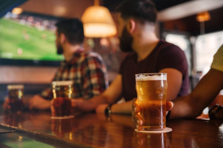Closeup of three young men drinking beer in bar and watching football match